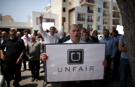 George, 35, protests with other commercial drivers with the app-based, ride-sharing company Uber against working conditions outside the company's office in Santa Monica, California June 24, 2014. REUTERS/Lucy Nicholson (UNITED STATES - Tags: BUSINESS EMPLOYMENT TRANSPORT CIVIL UNREST) - RTR3VKJ9