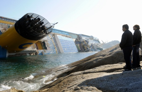 Two men look at a cruise ship that ran aground off the west coast of Italy at Giglio
