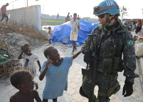 100316-N-9116F-001 PORT-AU-PRINCE, Haiti (March 16, 2010) A Brazilian U.N. peacekeeper walks with Haitian children during a patrol in Cite Soleil, a section of Port-au-Prince. Several U.S. and international military and non-governmental agencies are conducting humanitarian and disaster relief operations as part of Operation Unified Response after a 7.0-magnitude earthquake caused severe damage in and around Port-au-Prince, Haiti Jan. 12. (U.S. Navy photo by Mass Communication Specialist 1st Class David A. Frech/Released)