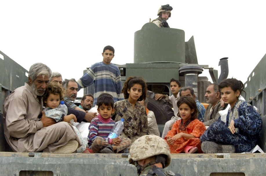 Displaced Iraqi civilians sit in an US Marine truck as they wait to be evacuated from the city of Fallujah 17 November 2004, 50 kms west of Baghdad, by a US Marine Civil Affairs unit.  US marines said today they expect to allow civilians back into Fallujah soon as they seek to restore normalcy to the battered city after more than a week of combat between US forces and rebels. AFP PHOTO/PATRICK BAZ