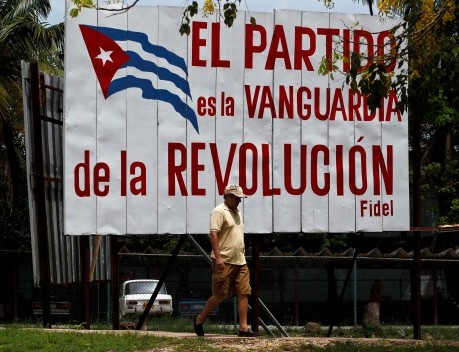 "A man walks past a banner that reads, ""The Cuban communist party is the vanguard of the revolution"" in Havana"
