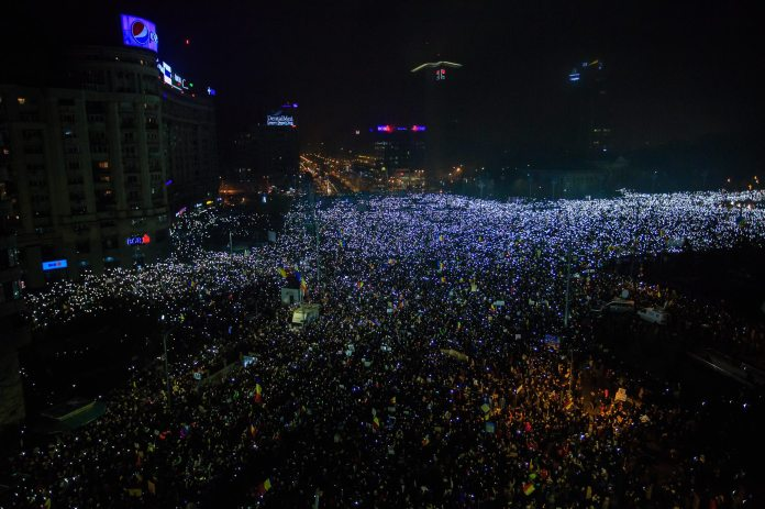 ( Aerial View of Protesters Lighting up their Phones at 10pm in front of the Romanian Government Building (February 2017 Demonstrations, Bucharest) © Marius Tudor, freelance photographer )