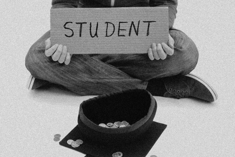 Male college student sitting cross-legged on the ground using a mortarboard graduation cap as a begging bowl.