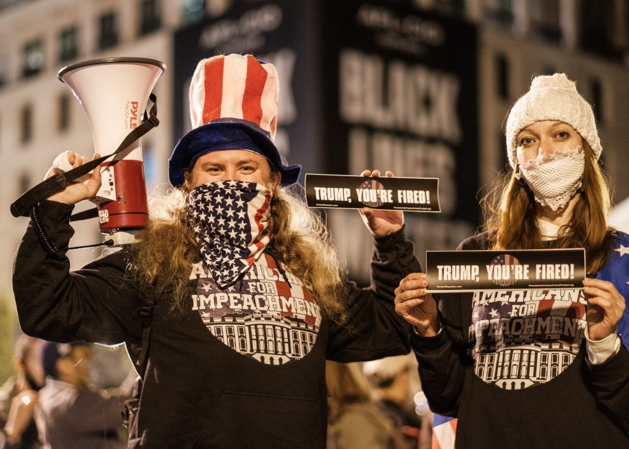 two people wearing americans for impeachment tops, one is holding a megaphone, boh are holding stickers that read trump you're fired and masks over their nose and mouth
